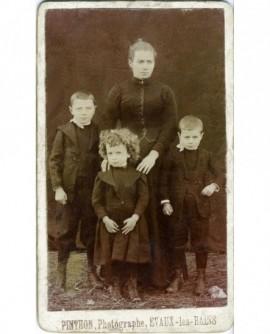 Femme en robe noire avec trois enfants