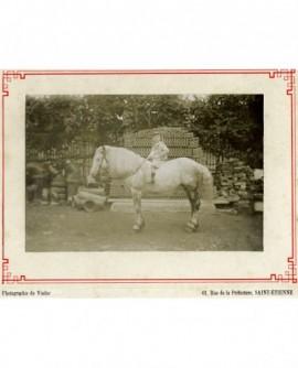 Jeune garçon sur un cheval dans la cour d'une tuilerie