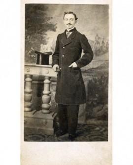 Homme debout ses gants à la main, son chapeau posé sur balustrade