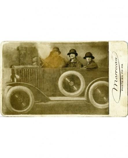 trois femmes en chapeau posant dans une torpédo (dans une foire)