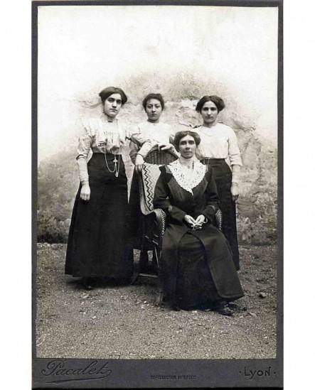 Femme en robe assise, mains jointes, entourée de trois jeunes filles en corsage blanc