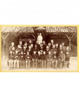 Groupe d'élèves autour d'un prêtre, devant une statue de St Joseph